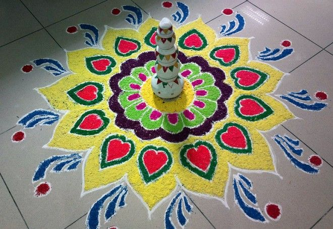 Colorful big rangoli design with flowers and heart shapes