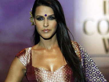Bollywood actress Dhupia displays a creation by Indian designer Kumar in Mumbai