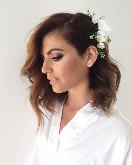Open wavy hairstyle with floral accessory