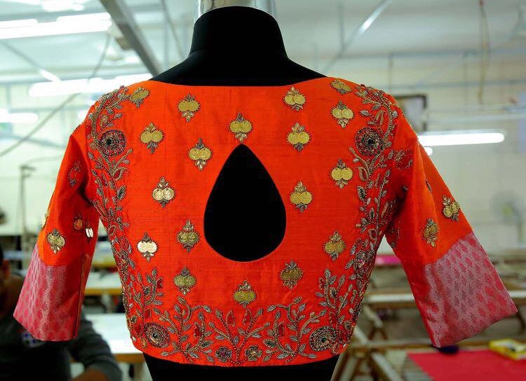 Orange blouse with red zari and maggam work
